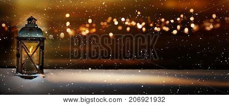 Burning lantern in a winter landscape with golden bokeh in the christmas night