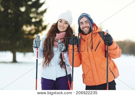 Young sweethearts skiing in forest together on winter weekend