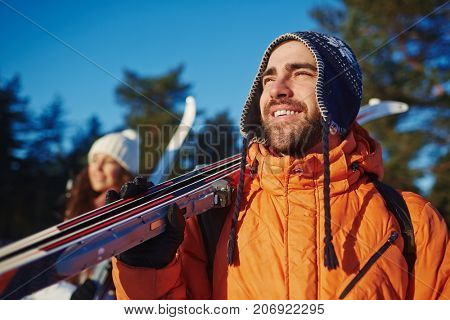 Smiling man with skis and his wife looking at something curious during trip in winter forest