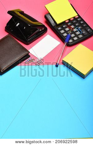 Office Tools And Leather Wallet On Pink And Blue Background