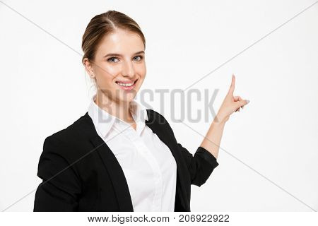 Smiling blonde business woman pointing back and looking at the camera over white background