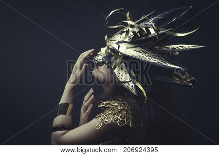 Jewelry, Girl in dress made of golden threads with golden mask, beautiful young brunette