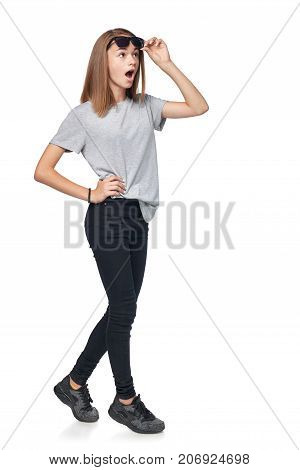 Surprised teen girl in full length looking with opened mouth away at blank copy space raising her sunglasses in astonishment, isolated on white background