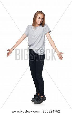 Teen girl in full length standing shrugging her shoulders, isolated on white background