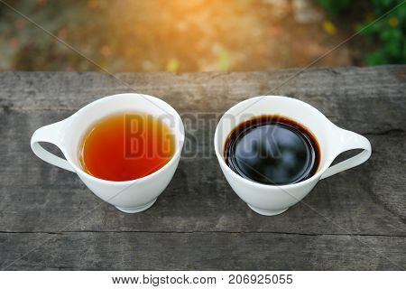 White cup of earl grey tea and coffee on wooden background in sunny morning