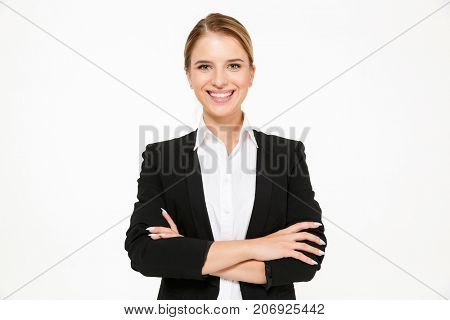 Smiling blonde business woman posing with crossed arms and looking at the camera over white background
