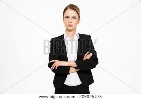 Displeased blonde business woman looking at the camera with crossed arms over white background