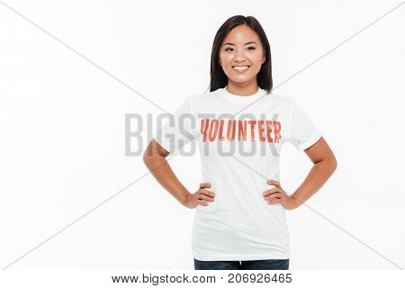 Portrait of a happy cheerful asian woman in volunteer t-shirt standing with hands on hips and looking away isolated over white background