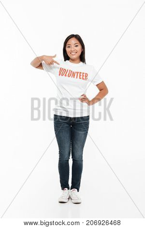 Full length portrait of a smiling young asian woman in volunteer t-shirt standing and pointing finger while looking at camera isolated over white background
