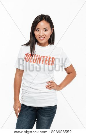Portrait of a smiling casual asian woman in volunteer t-shirt standing and looking at camera isolated over white background