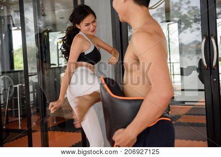 Girl Practice Muay Thai Kick To Boxing Mitt