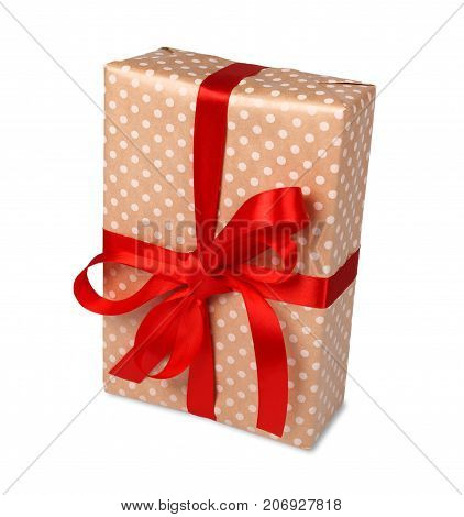 Gift box wrapped with dotted beige paper and red satin ribbon, isolated on white background. Modern present for any holiday, christmas, valentine or birthday