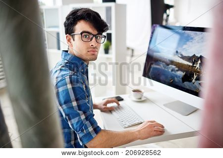 Serious young designer or retoucher sitting by workplace in front of computer and doing his work