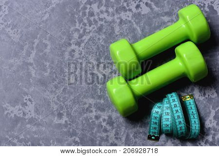 Measuring Tape Roll Next To Barbells. Dumbbells In Green Color
