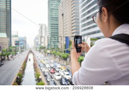 Chinese Woman taking photo with her smart phone on the traffic jam and buildings background in the city. Copy space.