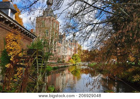 Castle reflection with windmill in autumn scenery - neo gothic castle in Heverlee, Leuven, Belgium