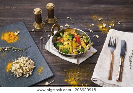 Healthy vegan food. Indian restaurant dish with fried tofu cheese, broccoli, mung bean and spices