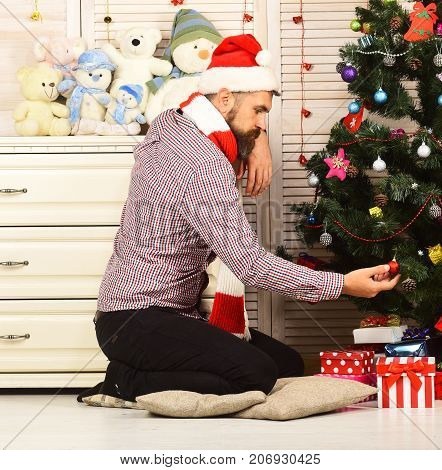 Guy In Hat And Scarf Sits By Fir Tree