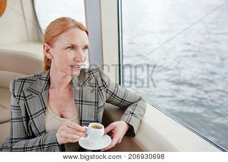 Serene businesswoman with drink enjoying coffee-break in steamship while looking through window