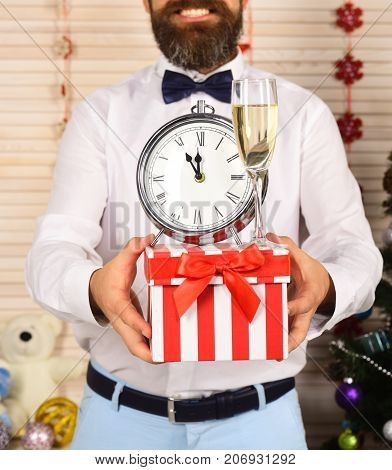 Guy Holds Striped Present Box With Champagne Glass And Clock