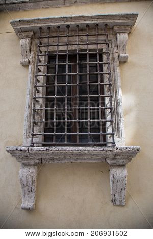 Old window protected by an iron safety grid.