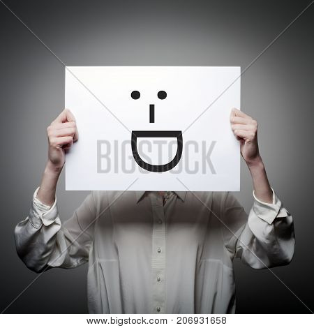 Woman is holding white paper with smile. Laughing and smiling concept.