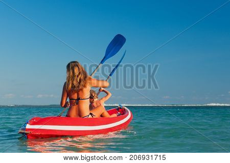 Happy family - mother baby daughter have fun on boat walk. Woman and child paddling on kayak. Travel lifestyle parents with kids recreational activity and water sports on summer sea beach vacation.