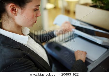 Young businesswoman making copies of financial documents on xerox