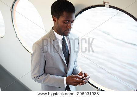 Well-dressed businessman with smartphone texting during travel on steamer