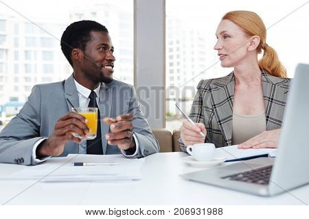 Intercultural colleagues communicating by drink during business travel