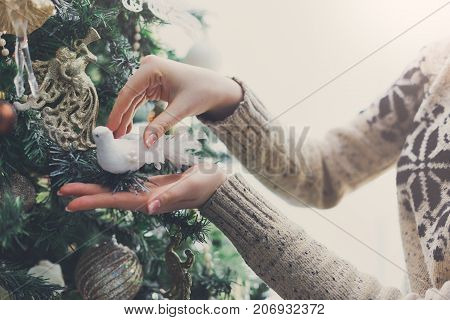 Female hands decorating christmas tree with toy bird figure. Stylish modern design, golden baubles, white beads and shiny garland. Winter holidays background with copy space