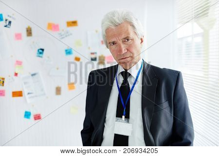 Waist-up portrait of confident mature police officer in classic suit looking at camera while investigating crime at modern office