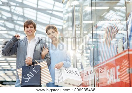 Young shopaholics with paperbags enjoying black friday sale in the mall