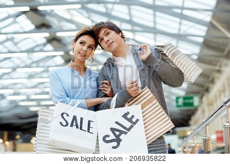 Affectionate dates with paperbags shopping in large modern trade center during sale