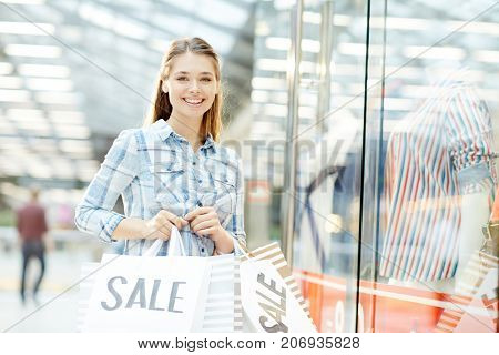 Modern custmer with paperbags standing by large window-display during shopping in trade center