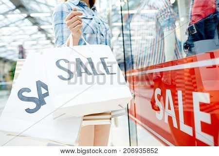 Shopper holds paperbags with sale announcement while standing by window display in modern mall
