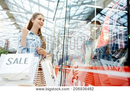 Modern young consumer looking at new collection of clothes in shop display