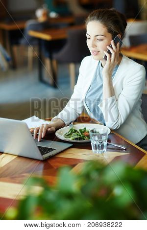 Young salesperson consulting client by phone while networking in cafe and having vegetarian salad and glass of water
