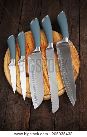 Set of five kitchen knives on wooden cutting board