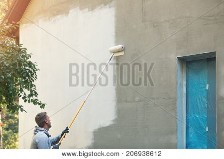 house painter painting building exterior with roller