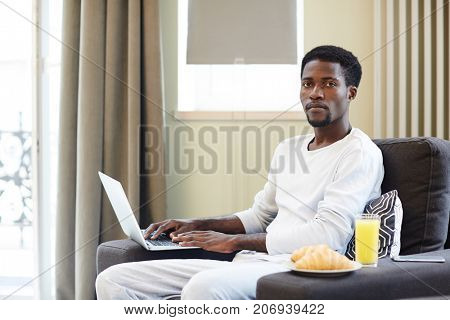 Portrait shot of confident African American man looking at camera while sitting on cozy armchair and checking business emails with help of laptop, appetizing breakfast on armrest