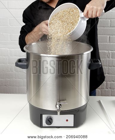 Homebrewing: a craft beer brewer adding barley to the kettle.