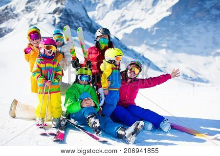 Family ski vacation. Group of skiers in Swiss Alps mountains. Adults and young children teenager and baby skiing in winter. Parents teach kids alpine downhill skiing. Ski gear and wear safe helmets.