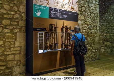 LONDON, GREAT BRITAIN - MAY 16, 2014:Unidentified tourists are considering a stand with early medieval weapons in the Armory Hall of the Tower of London.