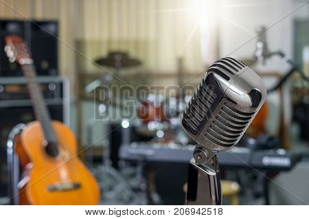 Retro Microphone over the Abstract blurred photo of music band instrument background musical concept