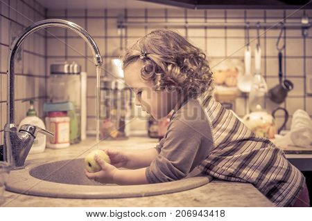 A cute little girl washes an apple in a sink in the kitchen.