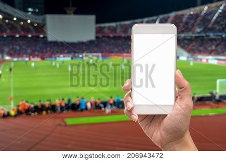 Female hand holding mobile smart phone touch screen on blurred of action photographer taking photo at player in Abstract blurred photo of soccer stadium sport background concept