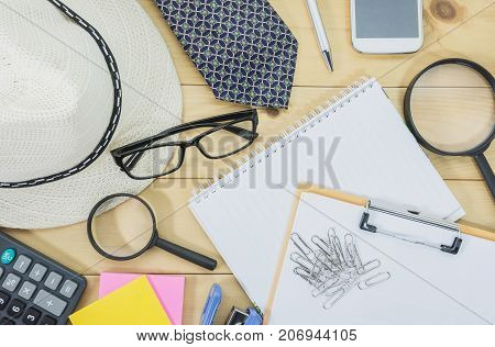 Office table top view with the glasses note book magnifying glass and mobile phone on desk cluttered. Cluttered office desk background.