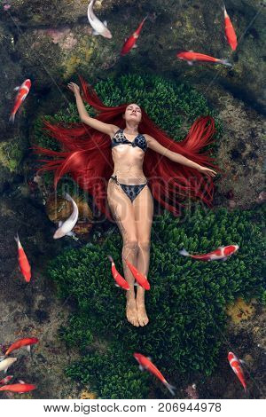 Surreal concept of young woman floating in water with fish