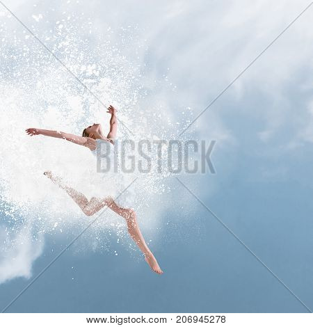 Beautiful ballet dancer jumping with cloud of powder in front of blue sky